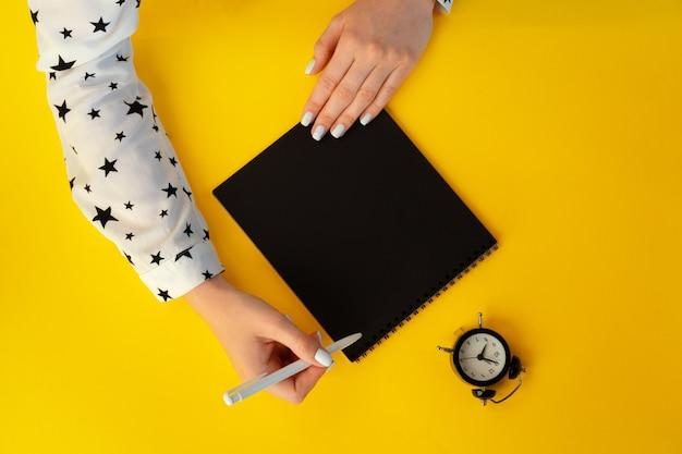 Vue de dessus des mains féminines écrivant dans le cahier