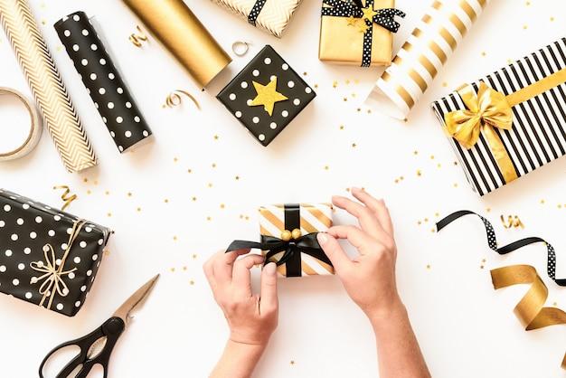 Vue de dessus des mains féminines emballant des boîtes-cadeaux, des matériaux d'emballage dispersés dans divers noir, blanc et or
