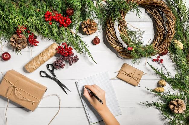 Vue de dessus des mains féminines envelopper des cadeaux emballés pour le nouvel an et faire défiler des branches d'épinette et des outils sur...