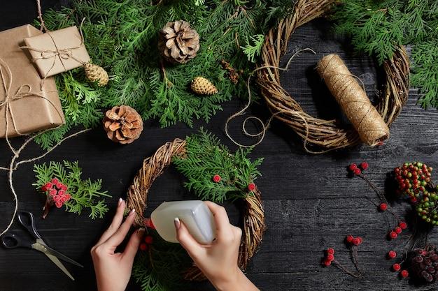 La vue de dessus des mains féminines fait une couronne de noël emballée des cadeaux et fait défiler des branches et des outils d'épinette ...
