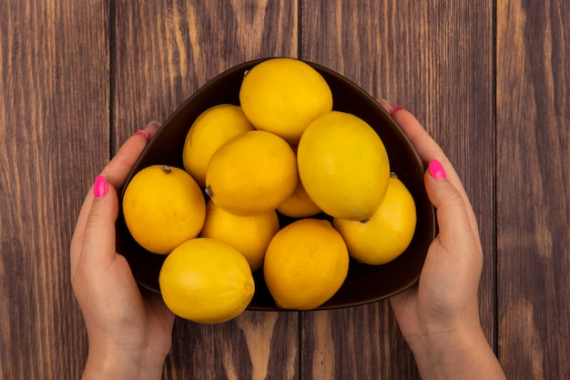 Vue de dessus des mains féminines tenant un bol de citrons frais sur un mur en bois