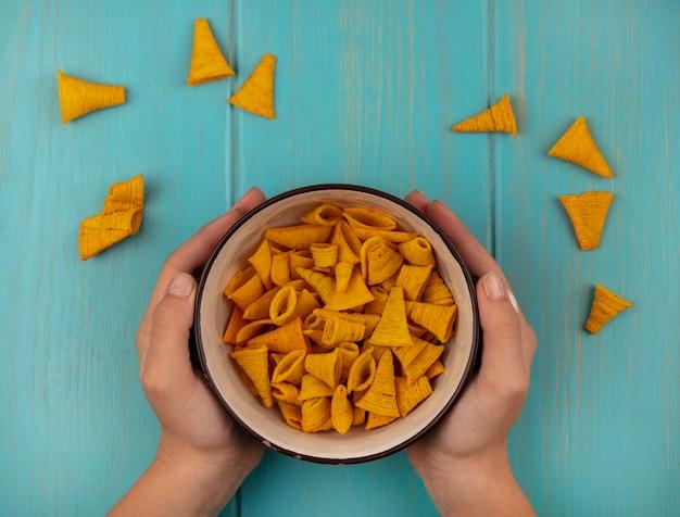Vue de dessus des mains féminines tenant un bol de délicieux collations de maïs en forme de cône sur une table en bois bleu