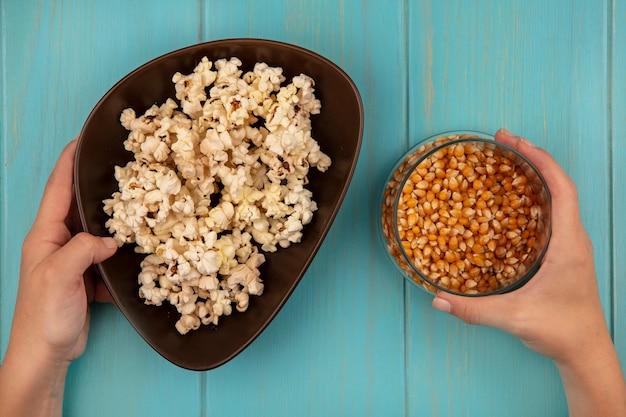 Vue de dessus des mains féminines tenant un bol de savoureux maïs soufflé dans une main et dans l'autre main un bol de grains de maïs soufflé sur une table en bois bleue