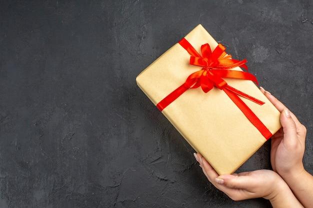 Vue de dessus des mains féminines tenant un cadeau de noël dans du papier brun attaché avec un ruban rouge sur une surface sombre