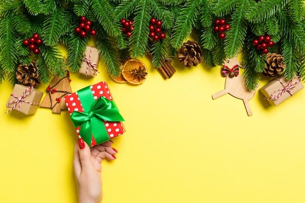 Vue de dessus des mains féminines tenant un cadeau de noël sur fond jaune festif