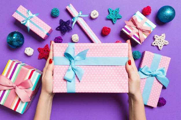 Vue de dessus des mains féminines tenant un cadeau de noël sur fond violet festif. décations de vacances, jouets et balles. concept de vacances du nouvel an