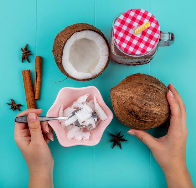 Vue de dessus des mains féminines tenant dans une main cuillère avec pulpes de noix de coco dans l'autre main de noix de coco entière avec cannelle et pot en verre sur bleu
