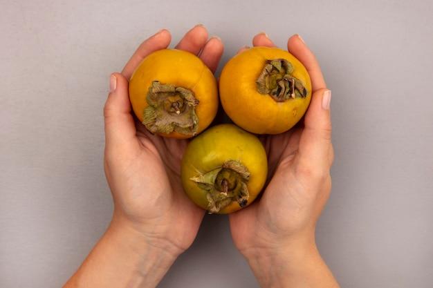 Vue de dessus des mains féminines tenant des fruits de kaki bio frais