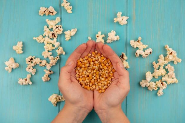 Vue de dessus des mains féminines tenant des grains de maïs soufflé avec du maïs soufflé isolé sur une table en bois bleu