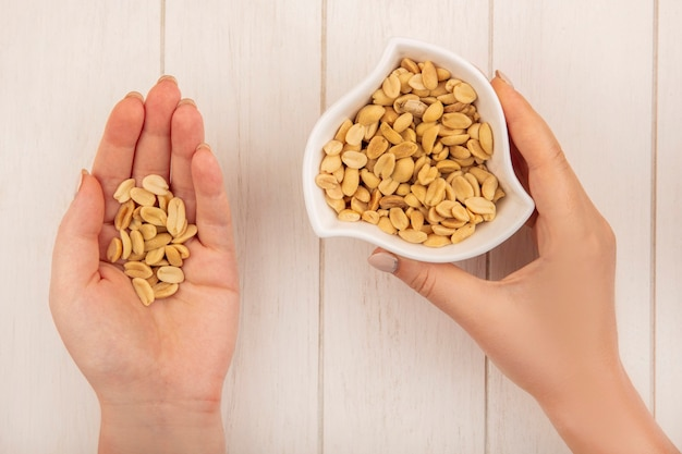 Vue de dessus des mains féminines tenant des pignons de pin salés dans une main et dans l'autre main le bol avec des pignons de pin sur une table en bois beige