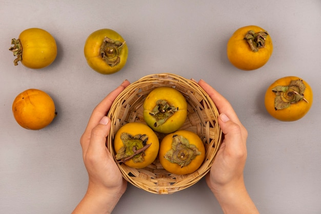 Vue de dessus des mains féminines tenant un seau de fruits kaki avec fruits kaki isolés
