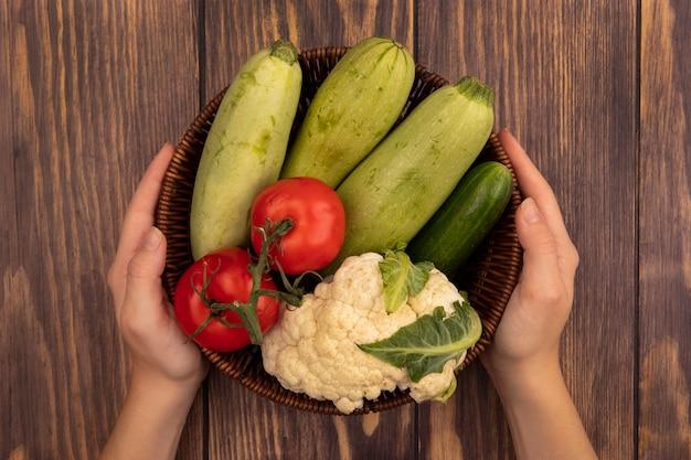 Vue de dessus des mains féminines tenant un seau de légumes frais tels que les courgettes tomates concombre et chou-fleur sur un mur en bois