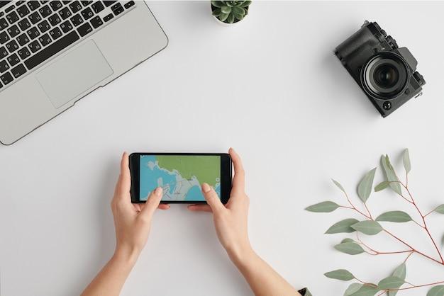 Vue de dessus des mains féminines tenant le smartphone avec carte à l'écran entouré d'un ordinateur portable et d'un appareil photo sur le bureau