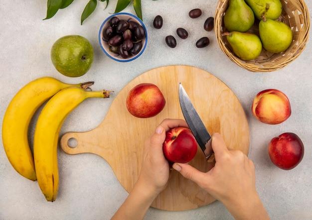 Vue de dessus des mains féminines trancher la pêche avec un couteau sur une planche à découper et pomme de banane poire raisin avec des feuilles sur fond blanc