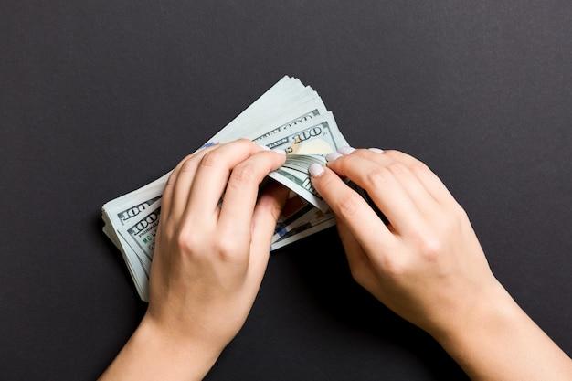 Vue de dessus les mains d'une femme d'affaires comptant des billets de cent dollars sur coloré. succès et richesse