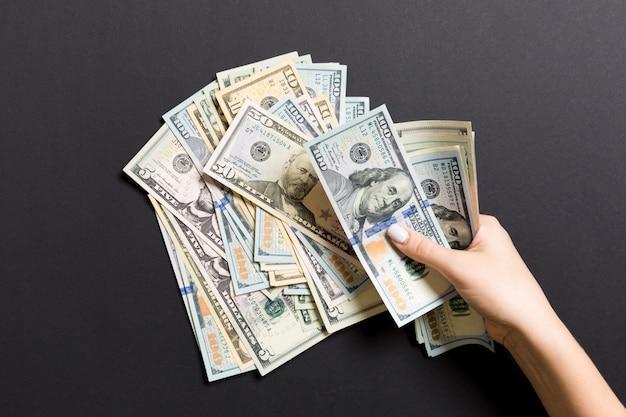 Vue de dessus des mains d'une femme d'affaires comptant cent billets de dollar différents