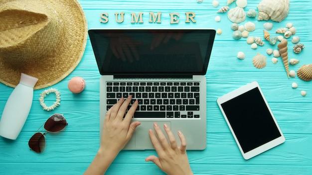 Vue de dessus des mains de femme à l'aide d'un ordinateur portable, accessoires d'été. fond de plage de vacances d'été, concept d'été de voyage