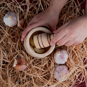 Vue de dessus des mains de femme en appuyant sur les gousses d'ail dans le broyeur d'ail et les bulbes d'ail autour sur fond de paille