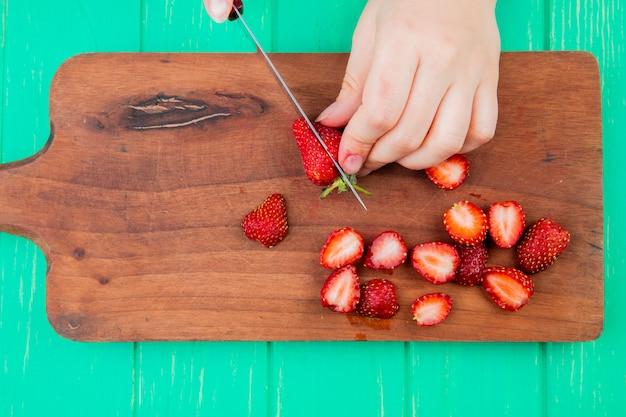 Vue de dessus des mains de femme coupant des fraises avec un couteau sur une planche à découper sur la surface verte