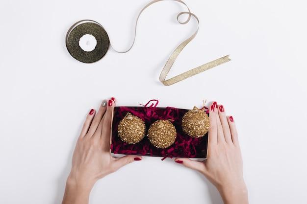 Vue de dessus des mains d'une femme avec du vernis à ongles rouge tenant une boîte de décorations de noël