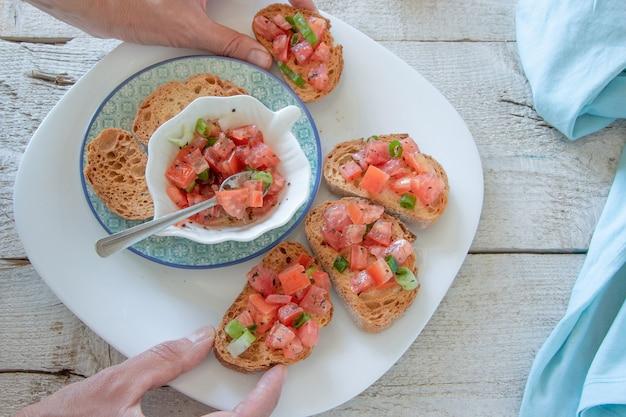 Vue de dessus des mains de femme préparant de savoureux apéritifs italiens à la tomate - bruschetta, sur des tranches de baguette grillée, vue rapprochée