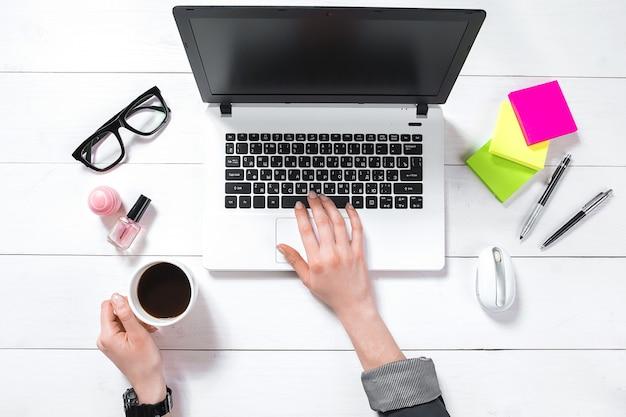 Vue de dessus des mains de la femme tapant sur un clavier d'ordinateur portable placé sur un bureau blanc avec une tasse à café. maquette
