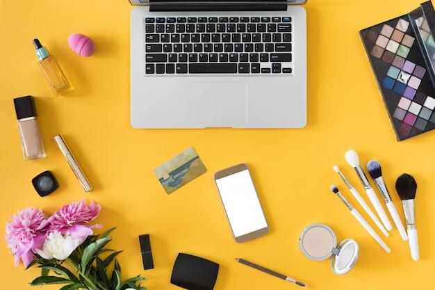 Vue de dessus des mains de femme tenant la carte de crédit, concept de magasinage en ligne, espace de travail beauté avec ordinateur portable, téléphone mobile, fleurs et ordinateur portable, plat poser.