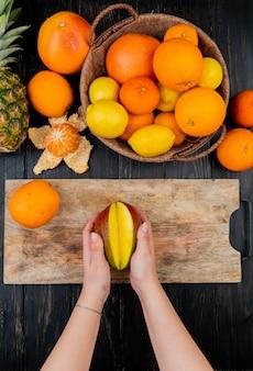 Vue de dessus des mains de femme tenant la mangue sur une planche à découper et des agrumes comme orange citron mandarine ananas sur table en bois
