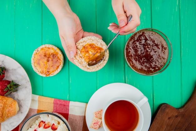 Vue de dessus des mains de femme tenant un pain croustillant croquant et une cuillère avec une tasse de thé, du fromage cottage de la confiture de pêches sur la surface verte