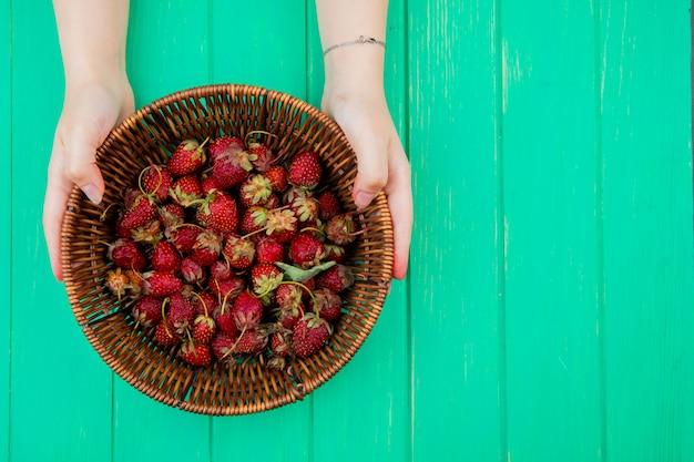 Vue de dessus des mains de femme tenant un panier avec des fraises sur le côté gauche et une table verte
