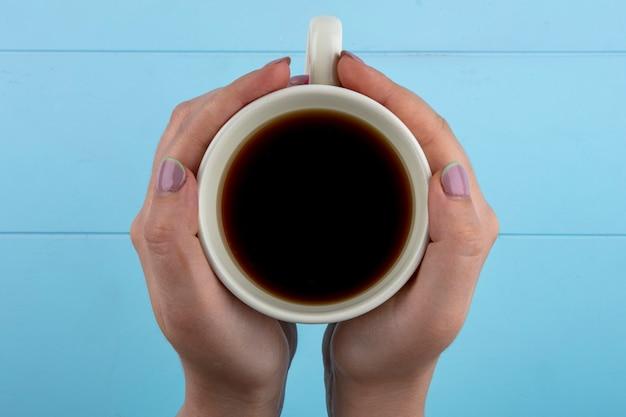 Vue de dessus des mains de femme tenant une tasse de thé sur fond bleu