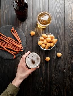 Vue de dessus des mains de femme tenant un verre de bière fond en bois noir