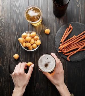 Vue de dessus des mains de femme tenant un verre de bière et de fromage snack fond de bois noir