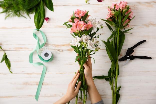 Vue de dessus des mains de fleuriste faisant le bouquet