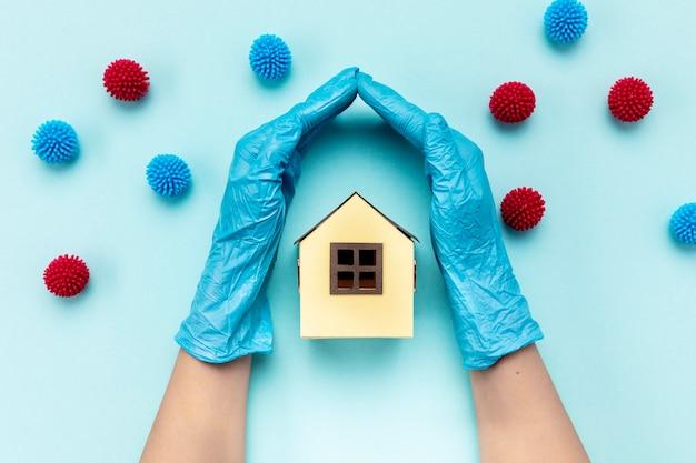Vue de dessus mains avec gant séparant les boules décoratives et maison en papier