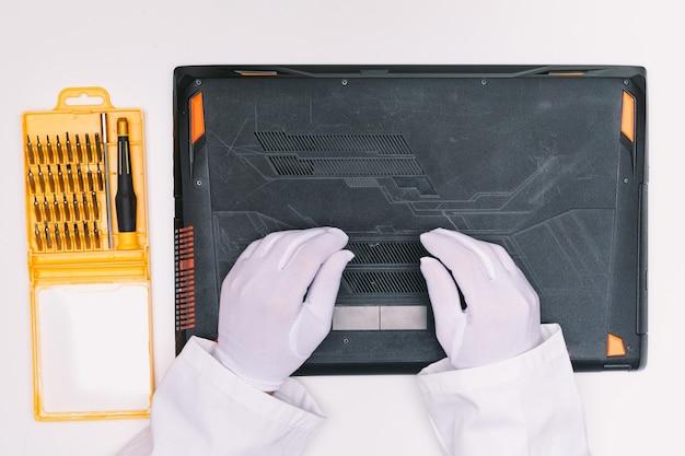 Vue de dessus des mains gantées de blanc d'un ingénieur, le dessous d'un ordinateur portable avant d'être réparé sur une table blanche