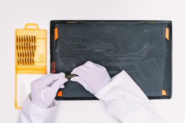 Vue de dessus des mains gantées de blanc d'un ingénieur dévissant les vis pour ouvrir le couvercle d'un ordinateur portable avant d'être réparé sur une table blanche