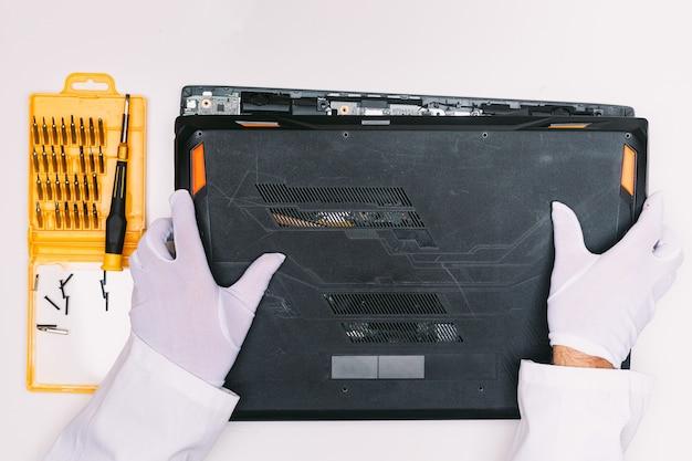 Vue de dessus des mains gantées de blanc d'un ingénieur, enlevant le couvercle d'un ordinateur portable avant d'être réparé sur une table blanche