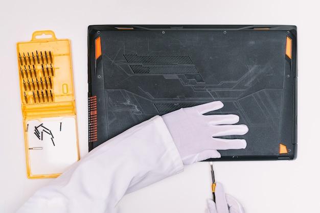 Vue de dessus des mains gantées de blanc d'un ingénieur, ouvrant le couvercle d'un ordinateur portable avec un tournevis avant d'être réparé sur une table blanche