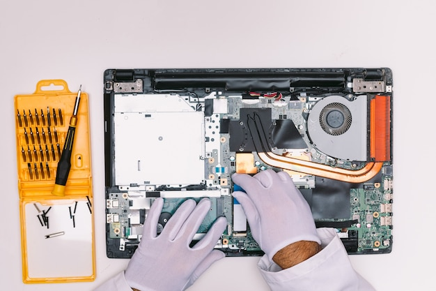 Vue de dessus des mains gantées de blanc d'un ingénieur, plaçant un disque dur ssd dans un ordinateur portable sur une table blanche