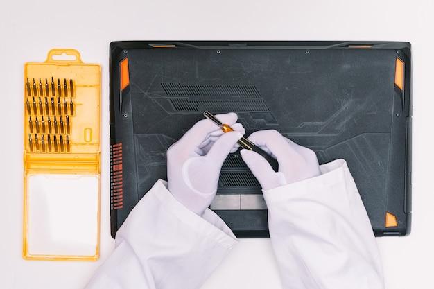 Vue de dessus des mains gantées de blanc d'un ingénieur, ramassant un tournevis pour ouvrir le couvercle d'un ordinateur portable avant d'être réparé sur une table blanche