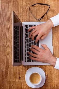 Vue de dessus des mains de l'homme à l'aide d'un ordinateur portable et en tapant.