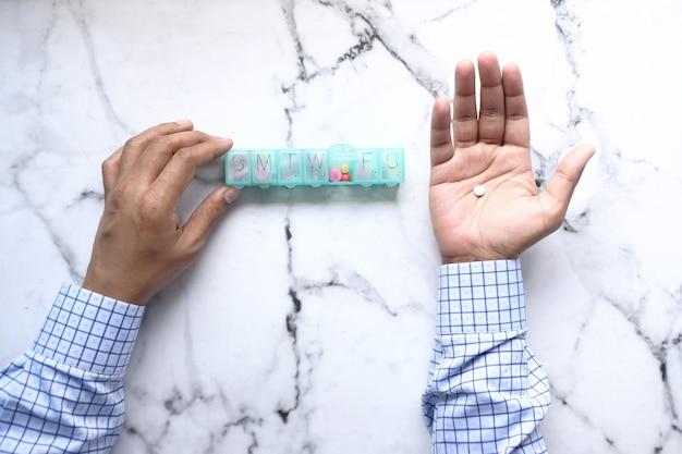 Vue de dessus des mains de l'homme prenant des médicaments à partir d'une boîte à pilules