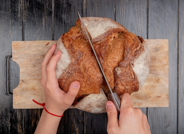 Vue de dessus des mains mâles couper le pain en épi avec un couteau sur une planche à découper sur fond de bois