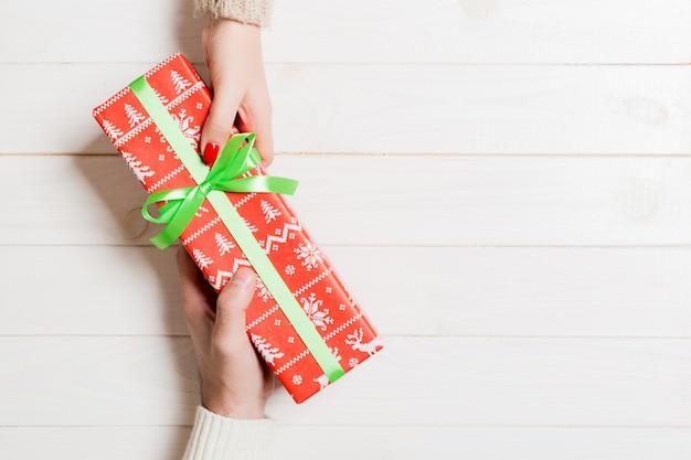Vue de dessus des mains mâles et femelles tenant la boîte présente sur bois. partager un cadeau. fond