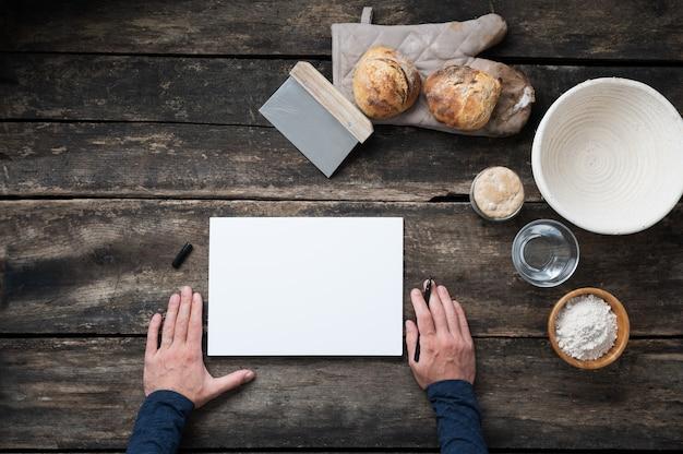 Vue de dessus des mains mâles sur le point d'écrire une recette pour un pain au levain sain fait maison sur un morceau de papier blanc avec tous les ingrédients placés autour d'elle sur un bureau en bois rustique.