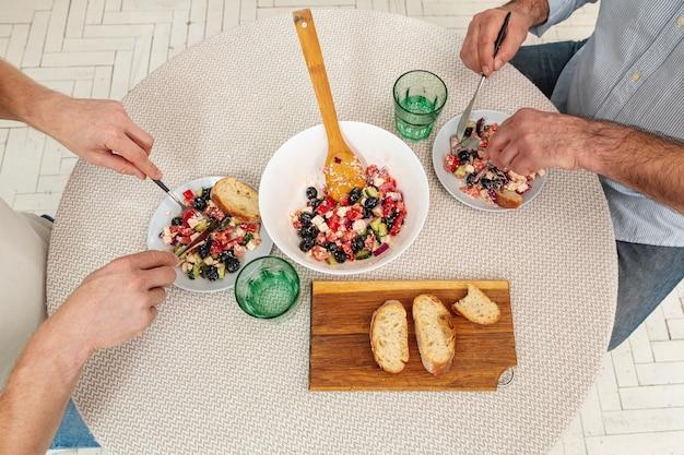 Vue de dessus des mains mâles servant une délicieuse salade