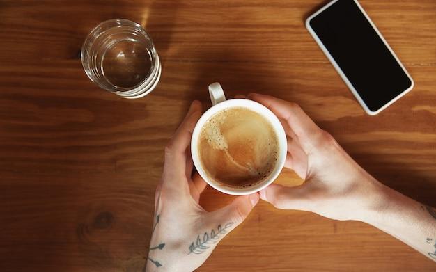 Vue de dessus des mains masculines à l'aide d'un smartphone avec écran blanc, espace de copie.