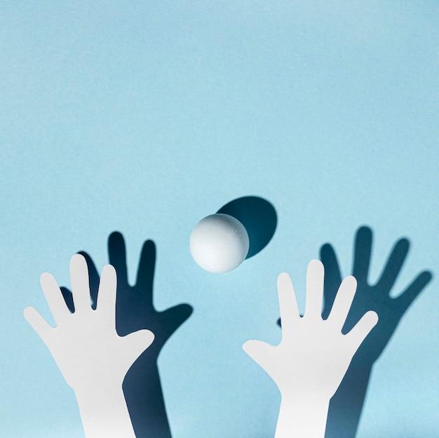 Vue De Dessus Des Mains De Papier Avec Balle De Ping-pong Photo gratuit