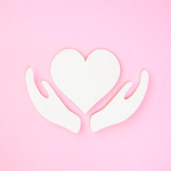 Vue de dessus des mains en papier avec coeur en papier